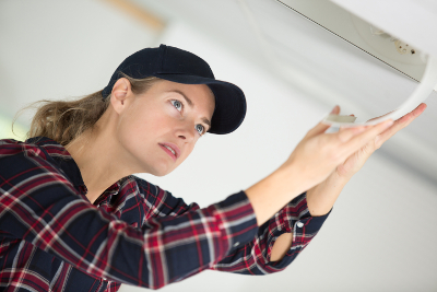 Air conditioning engineer inspects unit
